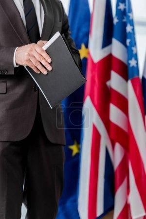 Photo pour Crochet d'un diplomate en costume tenant une chemise près des drapeaux - image libre de droit