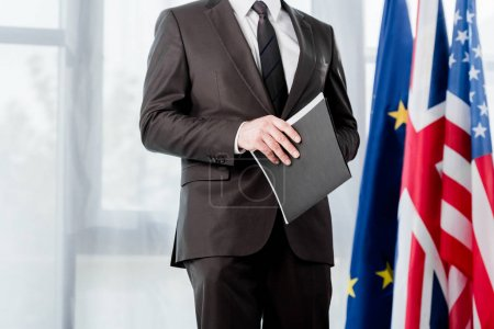 Photo for Cropped view of ambassador in suit holding folder near flags - Royalty Free Image