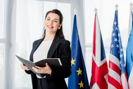 Photo for Happy diplomat in formal wear holding folder near flags - Royalty Free Image