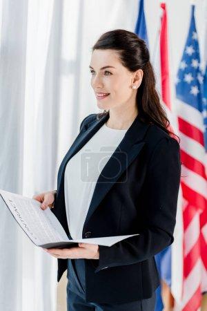 heureux diplomate tenant dossier avec contrat près du drapeau américain