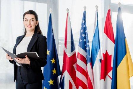 Photo pour Ambassadeur joyeux tenant dossier près de différents drapeaux - image libre de droit