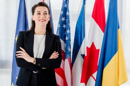 Photo pour Joyeux diplomate debout, les bras croisés près des drapeaux - image libre de droit