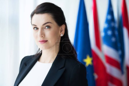 Photo for Attractive ambassador looking at camera near flags - Royalty Free Image