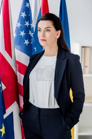 Photo pour Beau diplomate debout avec les mains dans les poches près des drapeaux - image libre de droit