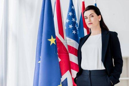 Photo pour Beau diplomate debout avec les mains dans les poches près des drapeaux et regardant la caméra - image libre de droit