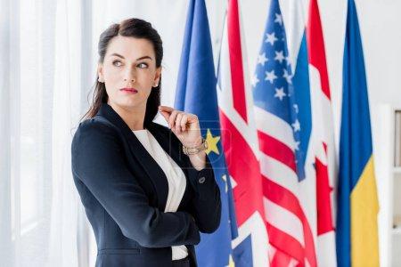 Photo pour Un diplomate attirant qui regarde loin près des drapeaux - image libre de droit