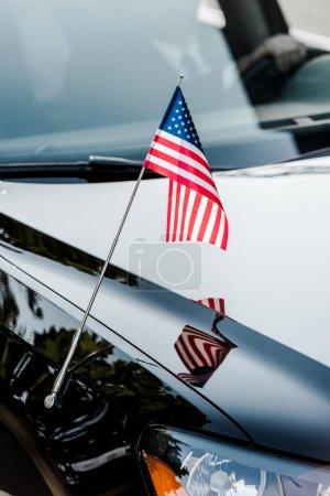 Photo pour Drapeau américain avec étoiles et rayures sur la voiture noire - image libre de droit