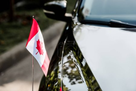 Photo for Selective focus of canadian flag with maple leaf on black car - Royalty Free Image