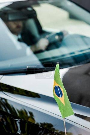 Photo pour Focalisation sélective du drapeau brésilien près de l'homme dans la voiture moderne - image libre de droit