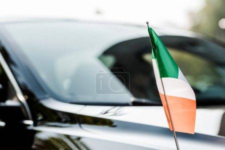 Photo pour Focalisation sélective du drapeau irisé près de la voiture noire moderne - image libre de droit
