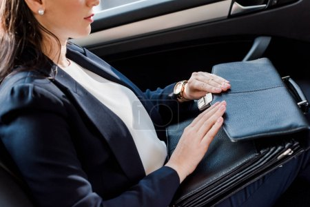 Photo for Cropped view of ambassador touching leather briefcase in car - Royalty Free Image