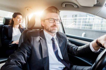 Photo pour Un diplomate gai conduit une voiture et regarde une caméra près d'une femme - image libre de droit