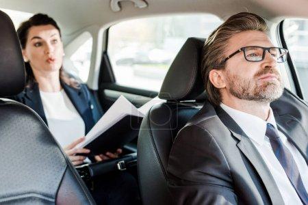 Photo pour Foyer sélectif de diplomate barbu assis dans la voiture avec une femme - image libre de droit