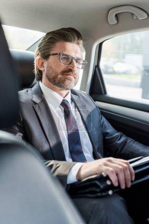 Photo pour Foyer sélectif de l'ambassadeur barbu tenant la mallette tout en étant assis dans la voiture - image libre de droit