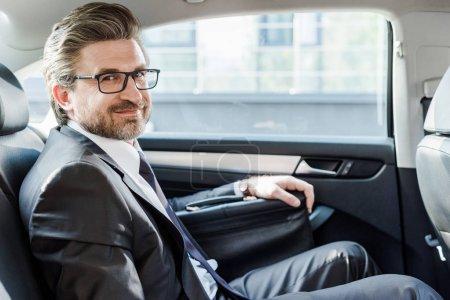 Photo pour Diplomate heureux dans des lunettes assis avec mallette dans la voiture - image libre de droit