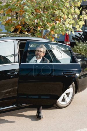 Photo for Handsome diplomat in glasses sitting in car with opened car door - Royalty Free Image