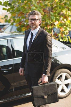 Photo pour Diplomate barbu dans des lunettes debout avec mallette près de la voiture - image libre de droit