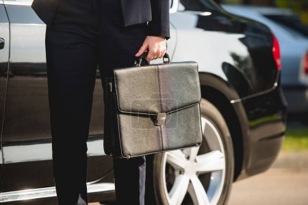Photo pour Vue recadrée de l'ambassadeur debout près de la voiture avec mallette - image libre de droit