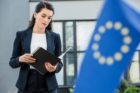 selective focus of attractive diplomat looking at folder near european union flag