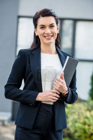 Photo pour Femme heureuse et attrayante tenant dossier près du bâtiment à l'extérieur - image libre de droit