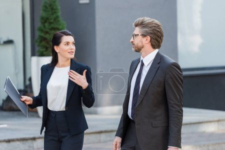 Photo for Attractive diplomat gesturing while looking at man in glasses and holding folder - Royalty Free Image