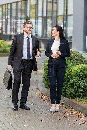 Photo pour Femme séduisante en tenue vestimentaire tenue dans une chemise et regardant un diplomate en lunettes dehors - image libre de droit