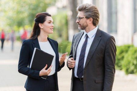 Photo pour Bel homme et jolie femme en tenue de cérémonie parlant à l'extérieur - image libre de droit