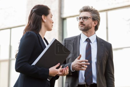 Photo for Attractive ambassador talking with handsome diplomat in glasses outside - Royalty Free Image