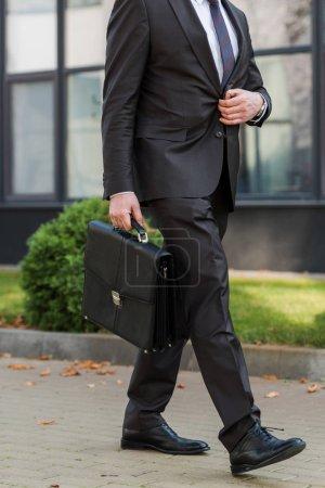 Photo pour Vue en coupe d'un diplomate touchant un blazer alors qu'il marchait avec un porte-documents - image libre de droit