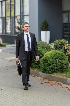 Photo for Handsome diplomat in glasses holding briefcase and standing near building - Royalty Free Image