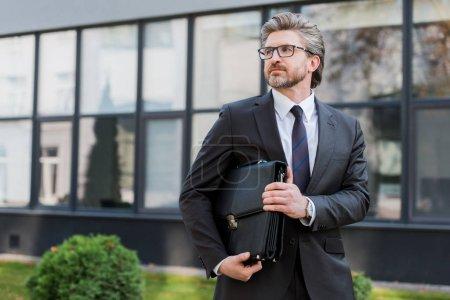 Photo pour Diplomate barbu dans des lunettes tenant la mallette en cuir et debout près du bâtiment - image libre de droit