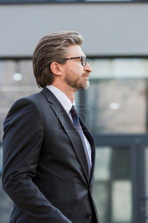 Photo pour Vue de côté d'un beau diplomate en lunettes debout près d'un immeuble - image libre de droit