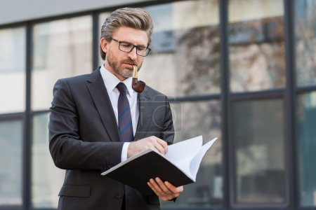 handsome diplomat smoking pipe and looking at folder with documents