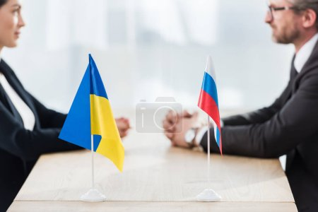 Photo for Selective focus of ukrainian and russian flags near ambassadors with clenched hands - Royalty Free Image
