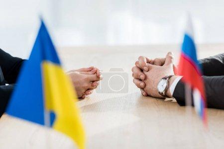 Photo pour Des ambassadeurs aux mains serrées près des drapeaux ukrainien et russe - image libre de droit