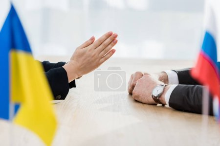 Photo pour Foyer sélectif du diplomate avec les mains priantes près de l'ambassadeur à l'ambassade - image libre de droit
