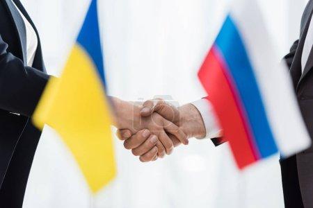 Photo pour Visages croisés de diplomates serrant la main près des drapeaux ukrainien et russe - image libre de droit