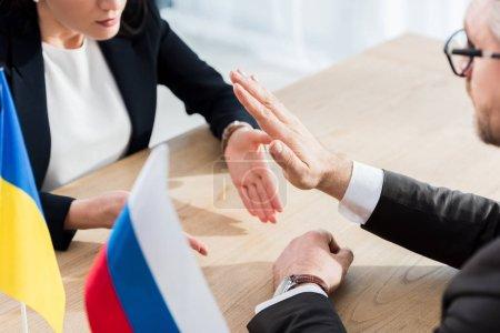 Photo pour Vue recadrée du diplomate ukrainien et ambassadeur de Russie dans les lunettes geste lors de la négociation - image libre de droit