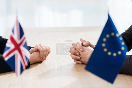 cropped view of ambassadors sitting with clenched hands near european union and united kingdom flags