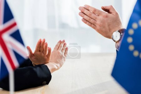 Photo pour Croix-gammée vue d'un diplomate de l'union européenne avec des mains de prière près de l'ambassadeur du royaume uni ne montrant aucun geste - image libre de droit