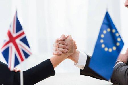 Photo pour Crochet vue des ambassadeurs tenant la main près des drapeaux de l'union européenne et du royaume uni - image libre de droit
