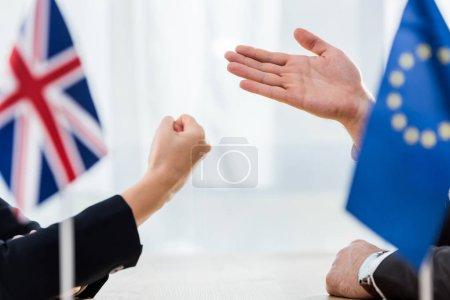 Photo pour Vue en demi-teinte d'un diplomate de l'union européenne près de l'ambassadeur du Royaume uni montrant le poing serré - image libre de droit