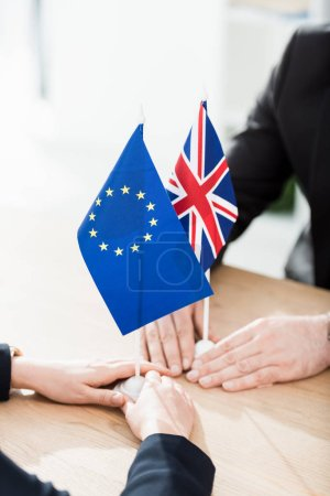 Photo for Cropped view of ambassadors touching european union and united kingdom flags on table - Royalty Free Image