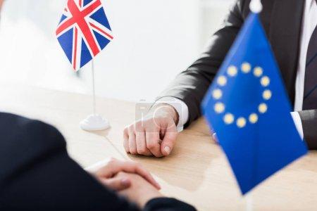 Photo pour Vue recadrée des ambassadeurs assis près de l'union européenne et des drapeaux du royaume uni - image libre de droit