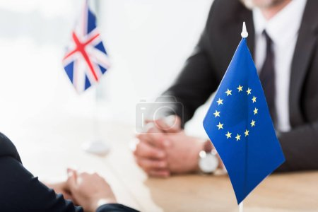 selective focus of european union flag near ambassadors with clenched hands