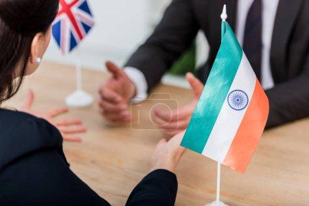 Photo pour Focalisation sélective de diplomates gesticulant près du drapeau de l'Inde et ambassadeur du Royaume uni - image libre de droit