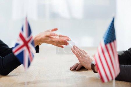 Photo pour Crochet vue de diplomates gesticulant près de drapeaux d'Amérique et de royaume uni - image libre de droit