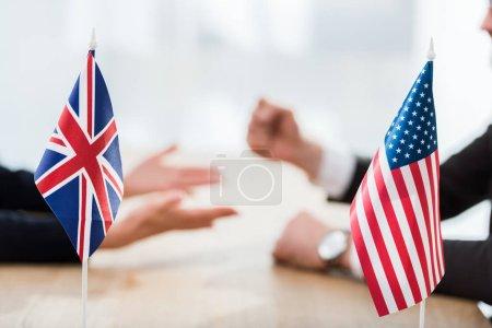 Photo pour Foyer sélectif des drapeaux des Etats-Unis et du royaume uni près des diplomates - image libre de droit