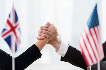 Photo for Selective focus of diplomats shaking hands near flags of usa and united kingdom - Royalty Free Image