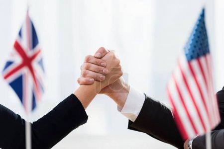 Photo pour L'attention sélective des diplomates serrant la main près des drapeaux de l'usa et du royaume uni - image libre de droit
